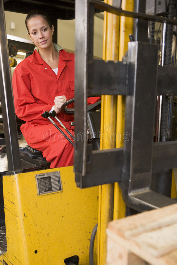 Warehouse worker in forklift. Warehouse worker driving a yellow forklift stock images