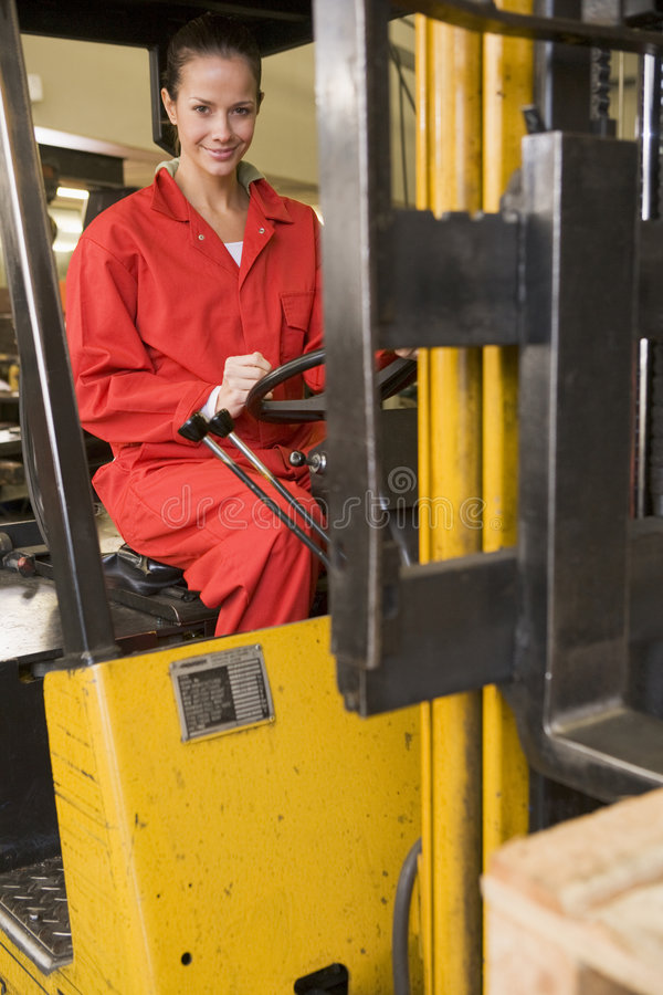 Warehouse worker in forklift. Warehouse worker driving a yellow forklift royalty free stock photos