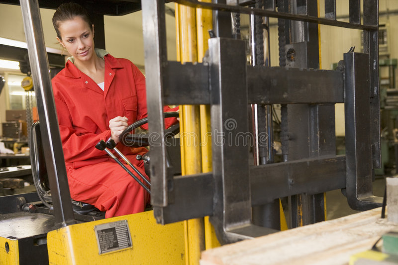 Warehouse worker in forklift. Warehouse worker driving a yellow forklift stock photography