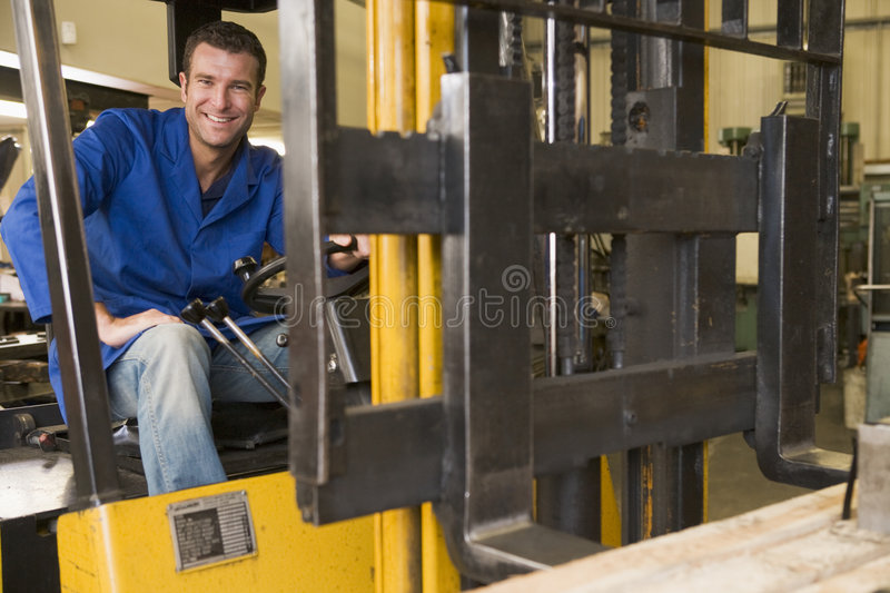 Warehouse worker in forklift. Warehouse worker driving a yellow forklift royalty free stock photo