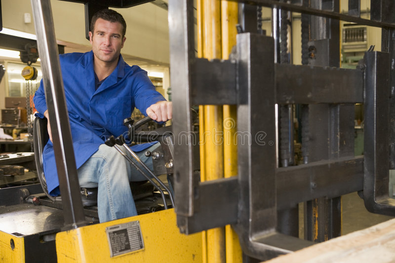 Warehouse worker in forklift. Warehouse worker driving a yellow forklift royalty free stock image