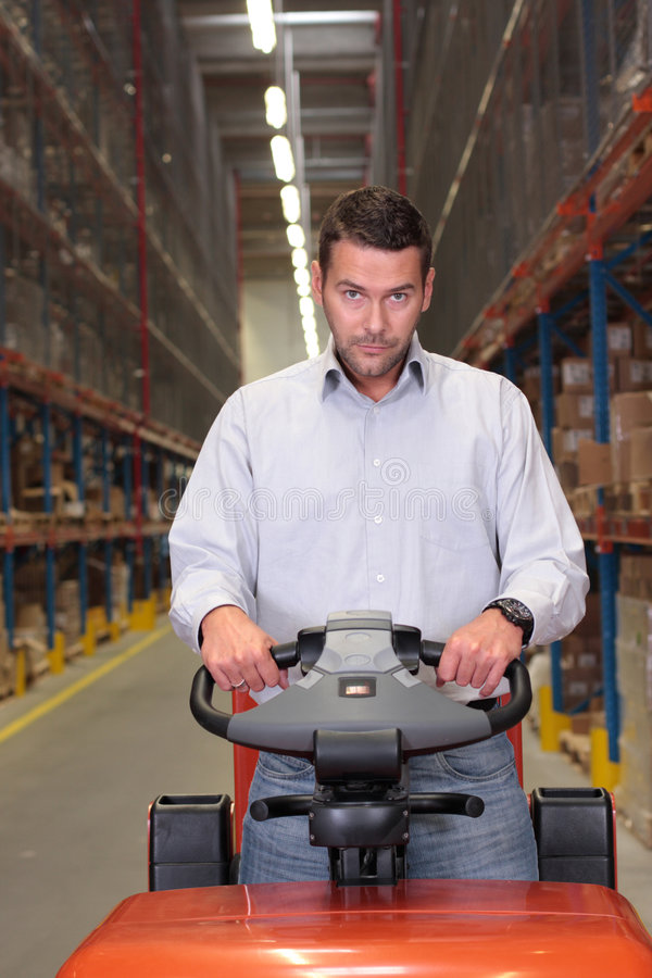 Warehouse worker on forklift. A male warehouse worker, driving a small forklift in the warehouse royalty free stock images