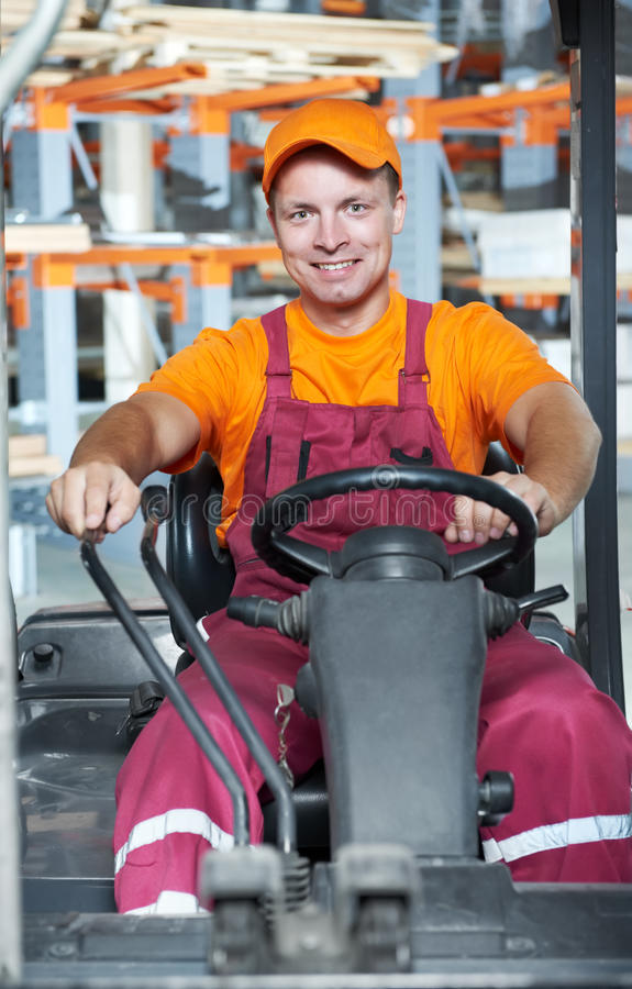Warehouse worker in forklift loader royalty free stock image