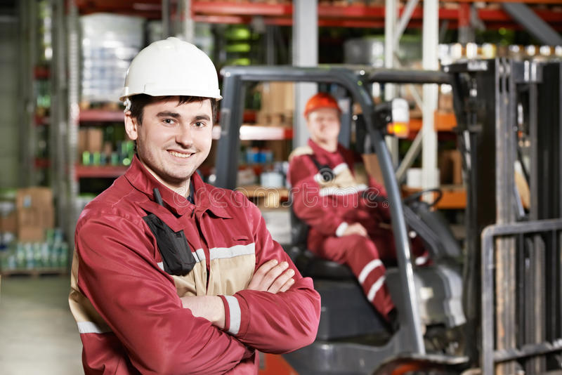 Warehouse worker in front of forklift. Young smiling warehouse worker driver in uniform in front of forklift stacker loader royalty free stock images