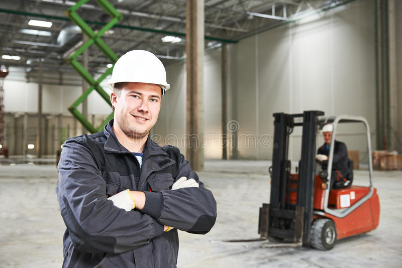 Warehouse worker in front of forklift. Young smiling warehouse worker driver in uniform in front of forklift stacker loader royalty free stock photo