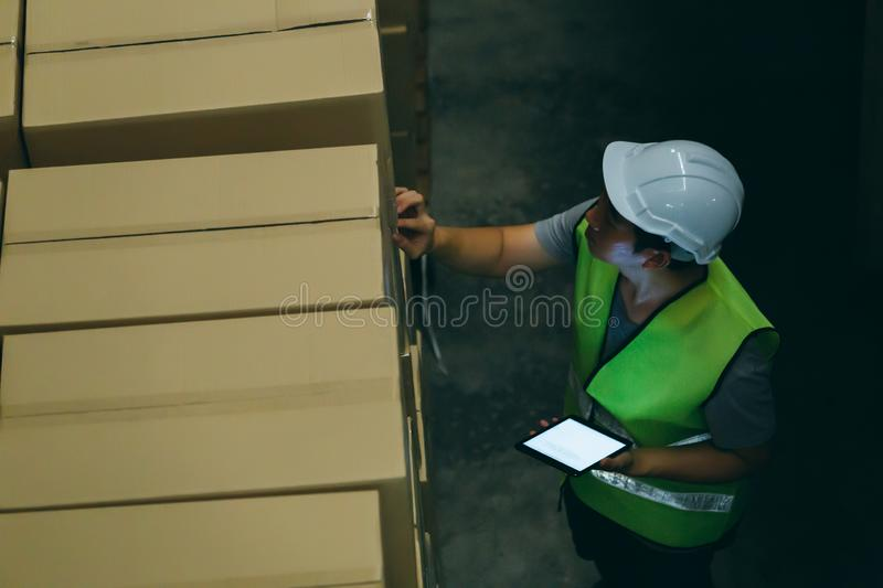 Warehouse worker man with safety hard hat is checking order details with a digital tablet at inventory room royalty free stock photos