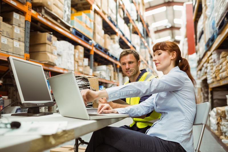Warehouse worker and manager looking at laptop. In a large warehouse royalty free stock photo