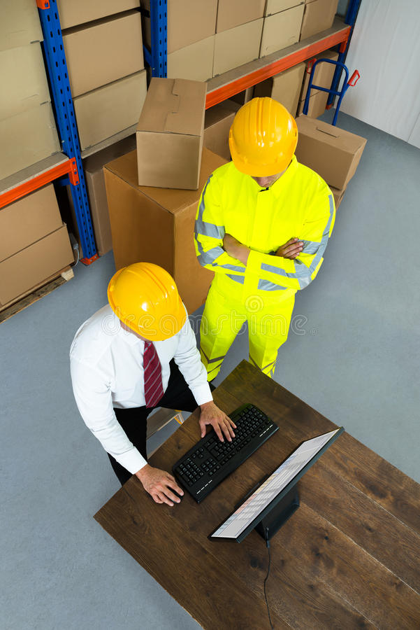 Warehouse Worker And Manager Using Computer. Elevated View Of Warehouse Worker And Manager Using Computer In A Warehouse royalty free stock image
