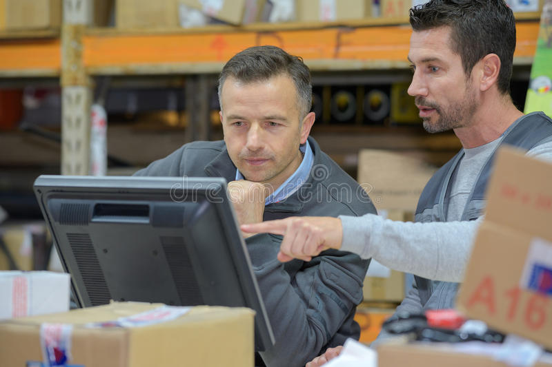 Warehouse worker and manager using computer in warehouse. Warehouse worker and manager using computer in a warehouse royalty free stock image
