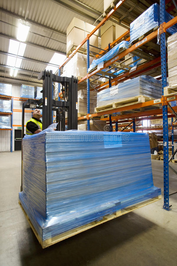 Warehouse worker moving boxes on pallet with forklift stock photography
