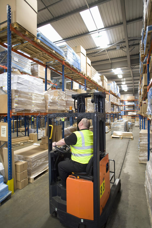 Warehouse worker operating forklift and looking up at shelves stock images