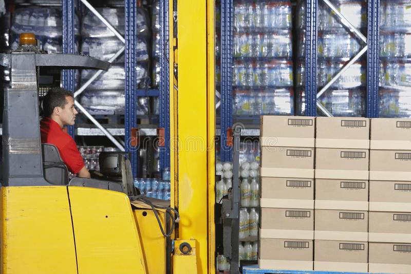 Warehouse Worker Operating Forklift. Side view of a warehouse worker operating forklift stock images