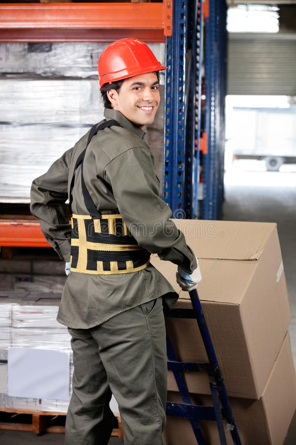 Warehouse Worker Pushing Handtruck royalty free stock image