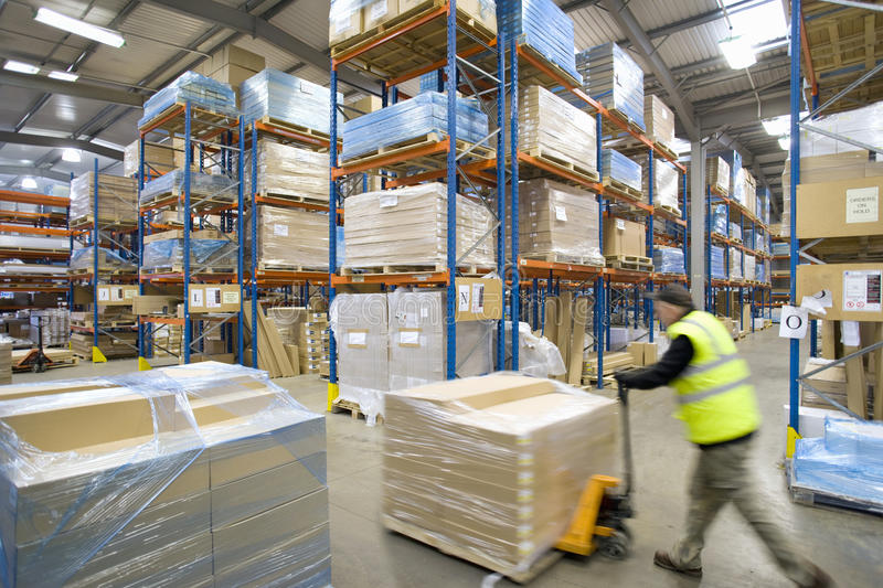 Warehouse worker pushing pallet truck with cardboard boxes royalty free stock image