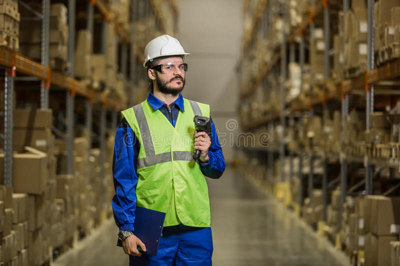 Warehouse worker with scaner looking at camera stock photography