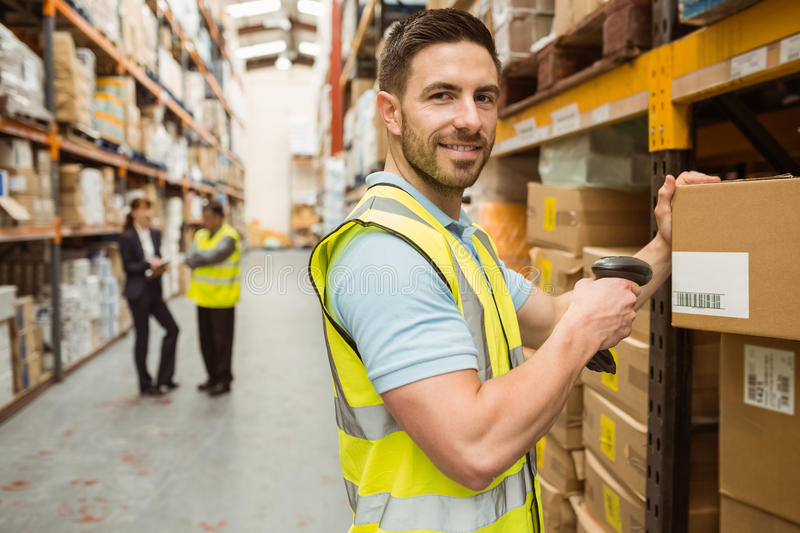 Warehouse worker scanning box while smiling at camera. In a large warehouse royalty free stock image