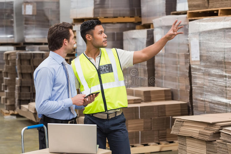 Warehouse worker showing something to his manager. In a large warehouse stock photos