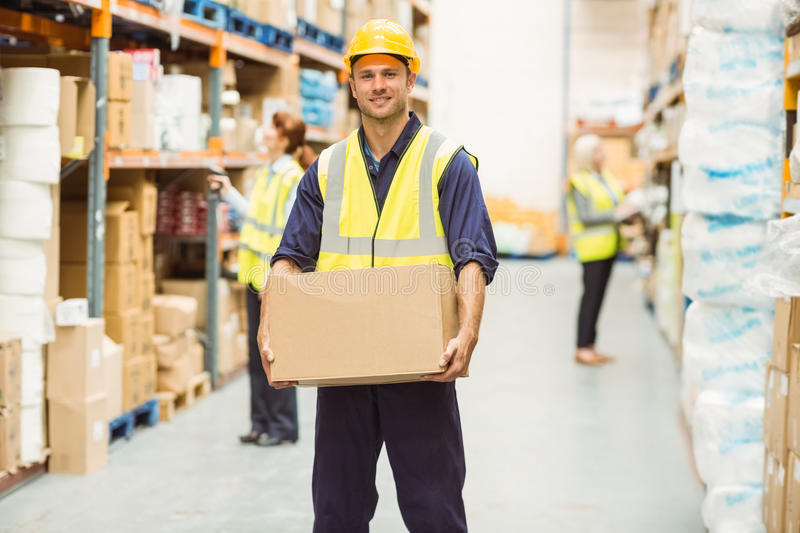 Warehouse worker smiling at camera carrying a box stock images