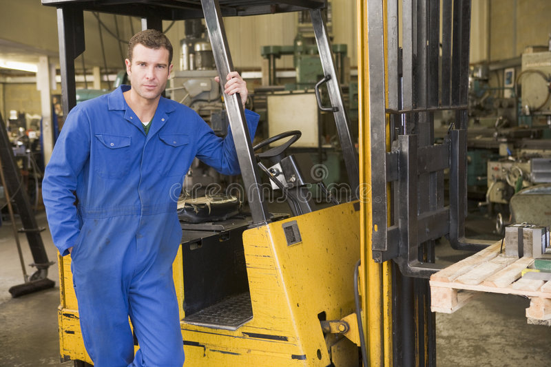 Warehouse worker standing by forklift. Warehouse worker standing by a yellow forklift stock images