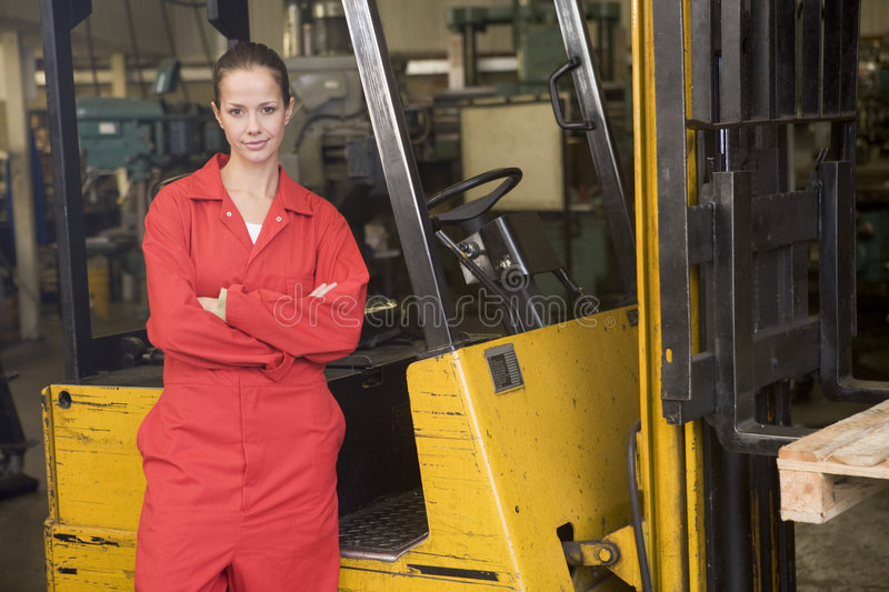 Warehouse worker standing by forklift. Warehouse worker standing by a yellow forklift stock photo