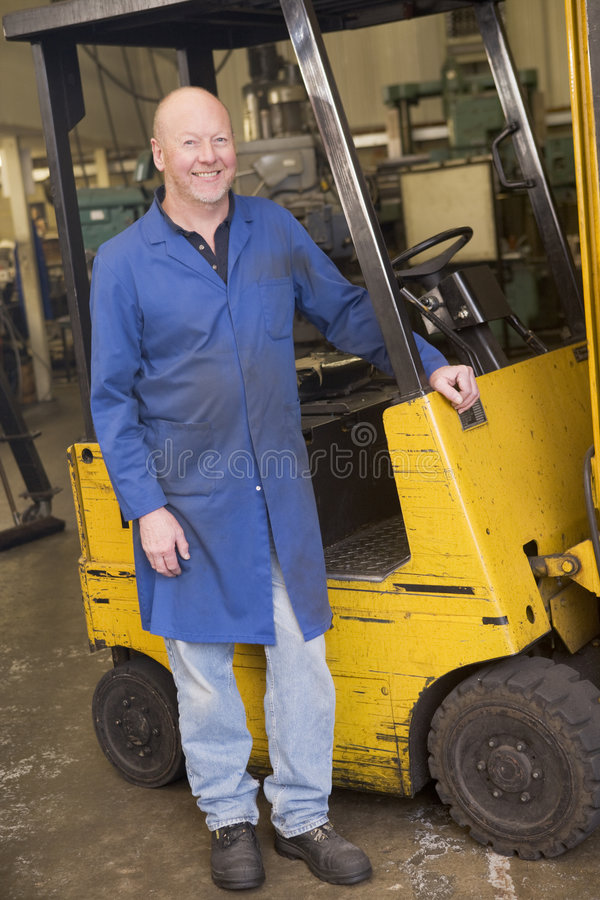 Warehouse worker standing by forklift. Warehouse worker standing by a yellow forklift royalty free stock image