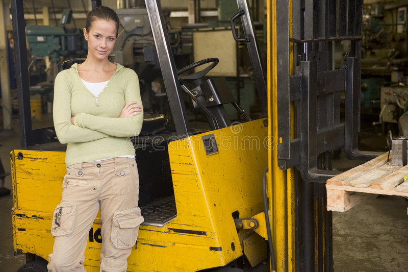 Warehouse worker standing by forklift. Warehouse worker standing by a yellow forklift royalty free stock photos