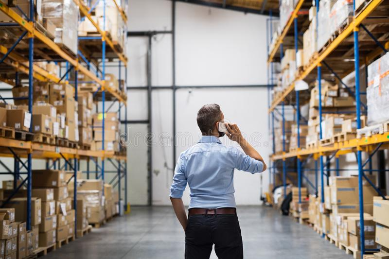 Warehouse worker or supervisor with a smartphone. royalty free stock photography