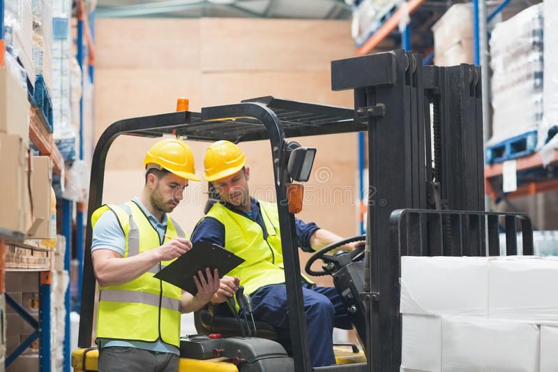 Warehouse worker talking with forklift driver. In warehouse stock photography