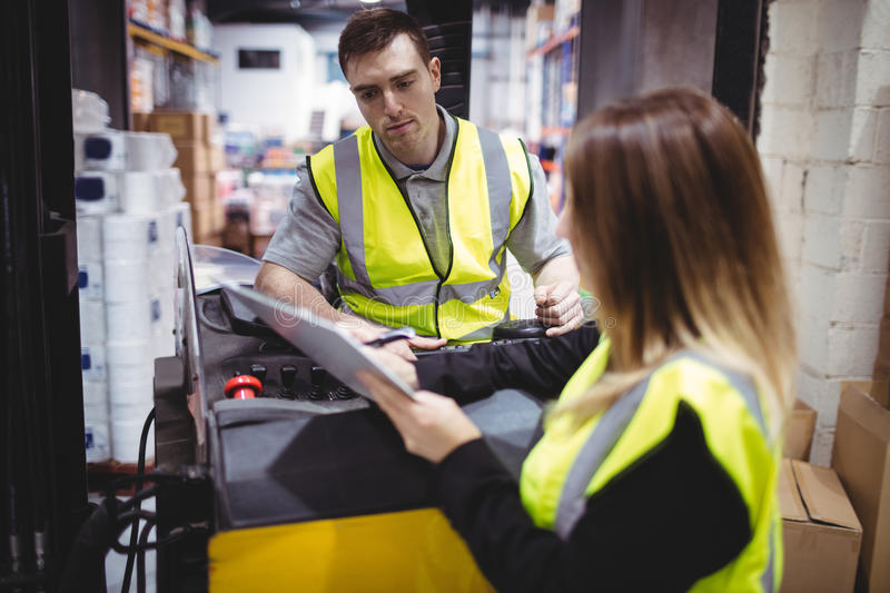Warehouse worker talking with forklift driver. In warehouse stock image