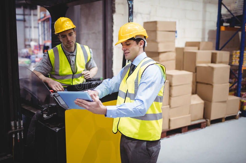 Warehouse worker talking with forklift driver. In warehouse royalty free stock photo