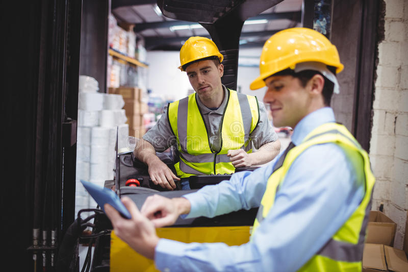 Warehouse worker talking with forklift driver. In warehouse stock photos