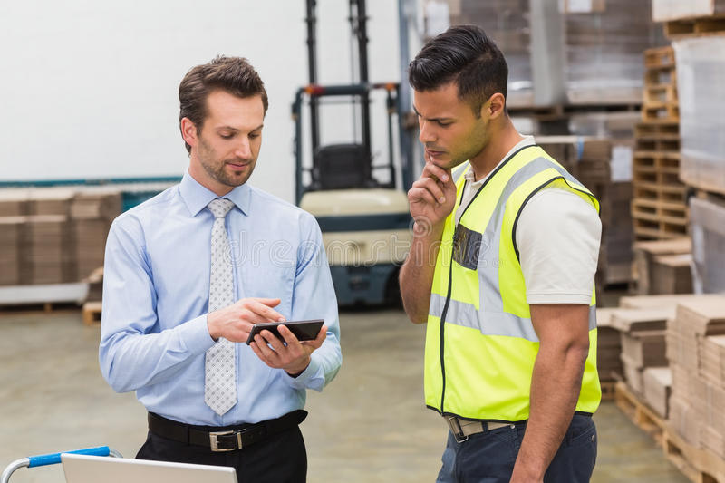 Warehouse worker talking with his manager. In a large warehouse royalty free stock images