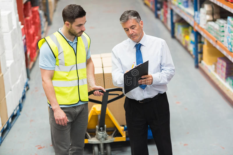 Warehouse worker talking with his manager. In a large warehouse stock image