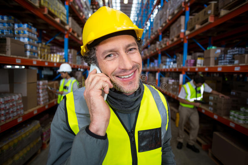 Warehouse worker talking on mobile phone stock photos