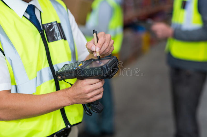 Warehouse worker using barcode scanner machine royalty free stock image