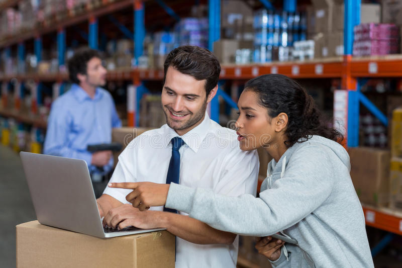 Warehouse worker working on laptop royalty free stock photography