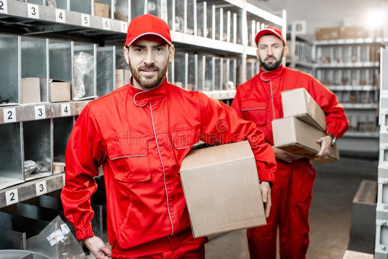 Warehouse workers with boxes indoors stock image