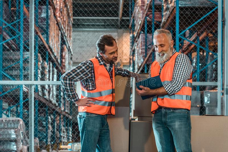 Warehouse workers taking notes in clipboard while working together. In storehouse royalty free stock image
