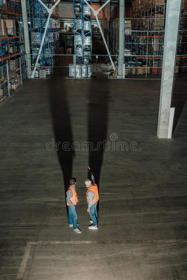 high angle view of two warehouse workers in vests talking while royalty free stock photos