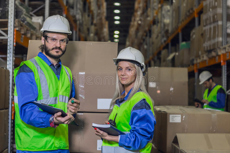 Warehouse workers looking at camera stock images