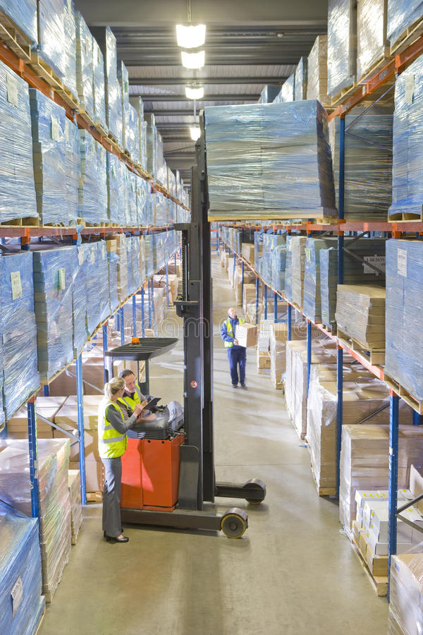 Warehouse workers moving boxes from shelf with forklift royalty free stock photography