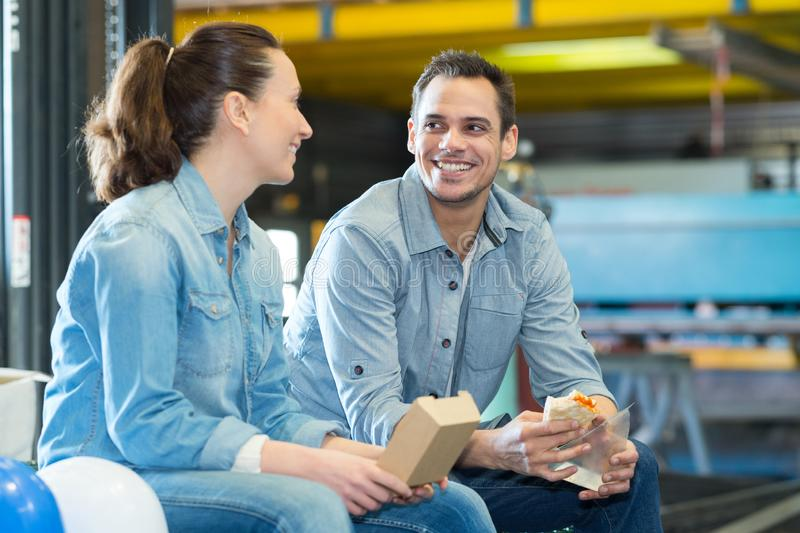 Warehouse workers sitting on pallets for lunch break stock image