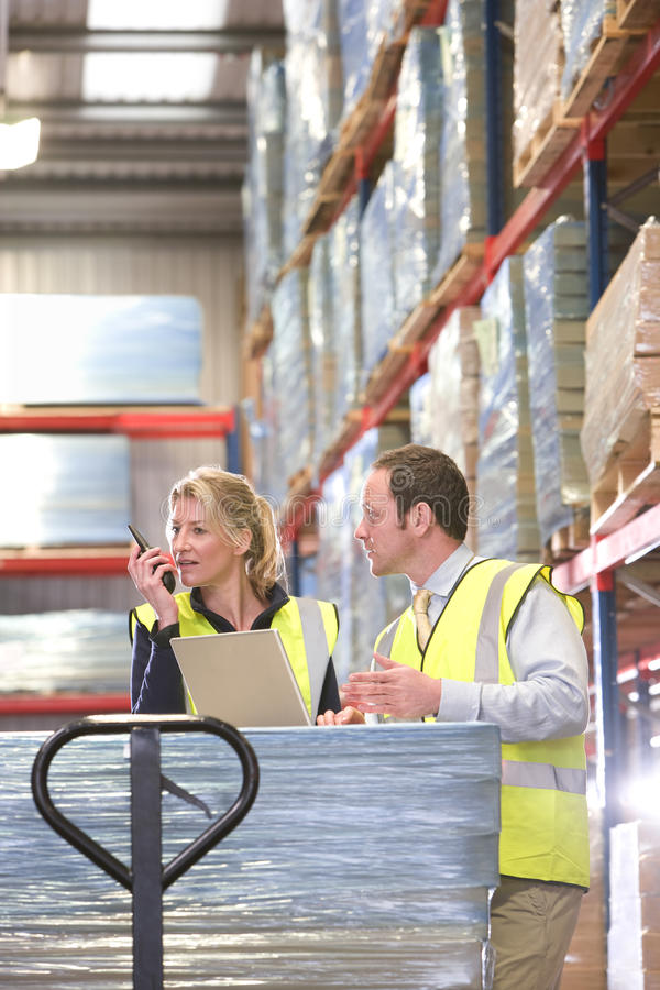 Warehouse workers with walkie-talkie and laptop on pallet truck royalty free stock photos
