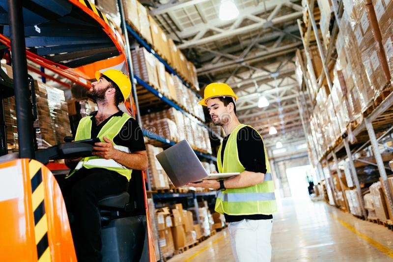 Warehouse workers working together with forklift loader. Trasnporter stock image