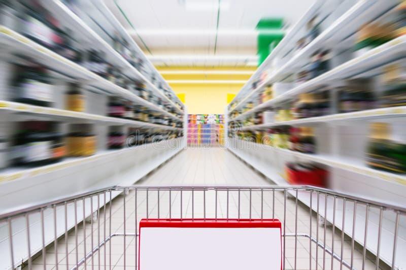 Warenkorb-Ansicht über einen Supermarkt-Gang und Regale - Bild hat flache Schärfentiefe stockbild