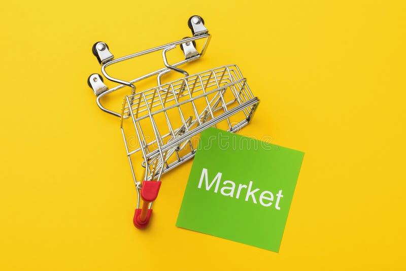 Warenkorb mit Invertiertem Lebensmittelgeschäft und Text auf gelbem Hintergrund Das Konzept fallender Märkte stockfotografie