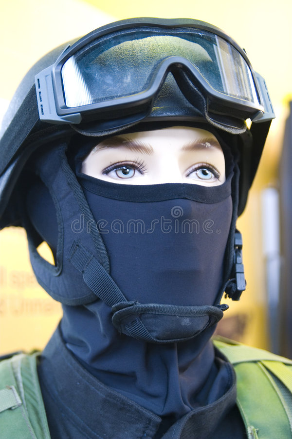 Warfare apparel. A closeup view of a model wearing modern warfare clothing and headgear including a camouflaged uniform, face covering, helmet and goggles royalty free stock photography