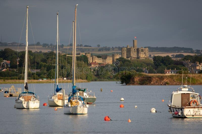 Warkworth城堡和被停泊的游艇看法在ea的缓行小游艇船坞 库存照片