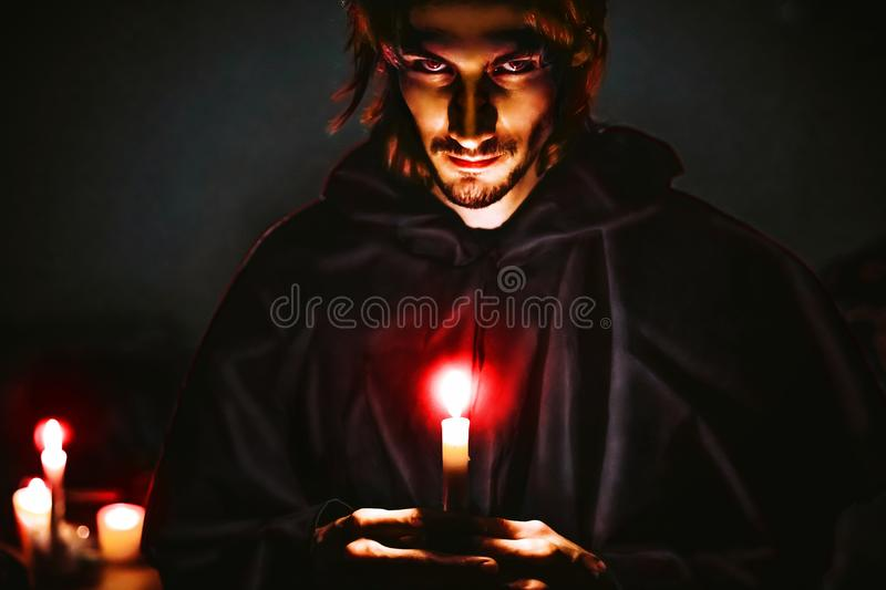 Evil sorcerer with a candle. Warlock with a candle in the dark scary look stock photography