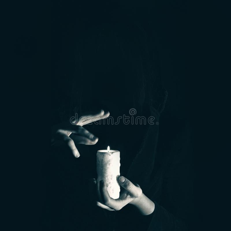 Warlock holds hands over burning candle in darkness, witchcraft stock photos
